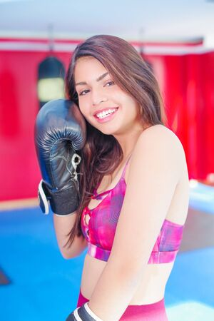 Young woman with dark hair with boxing gloves and punching bag in the back