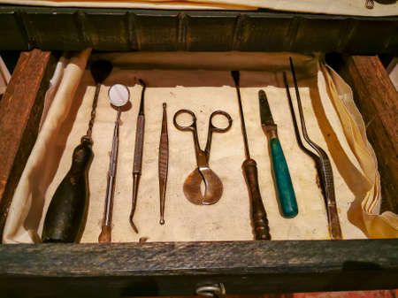 Set of colonial vintage medical instruments on a white cloth. The concept of the past medicine.