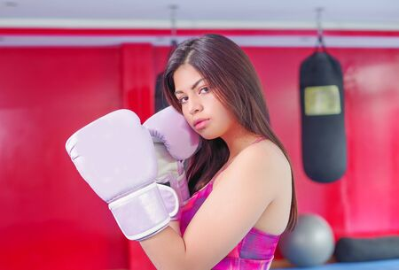 Sporty woman with dark hair in sports gloves and purple outfit for boxing in the gym.
