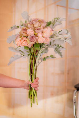 Women hand holding a bouquet of Pink roses and green foliage variety, studio shot, pink flowers