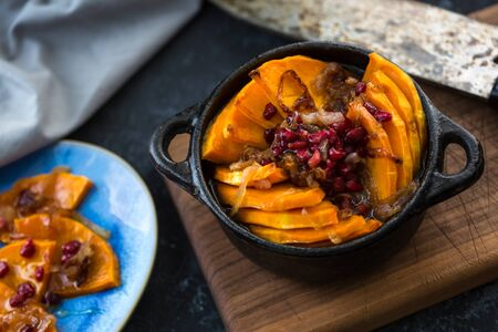 Grilled pumpkin with pomegranate, onion and honey. Baked with white wine pumpkin on the kitchen table