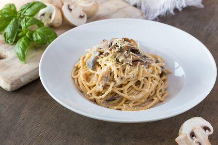 Mushroom Spaghetti Pasta and cream sauce on table, top view. Homemade italian pasta with champignon mushroom.