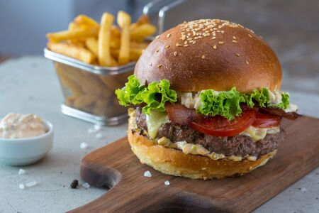 Highigh burger with french fries in small fry basket on concrete surface. Traditional American fastfood