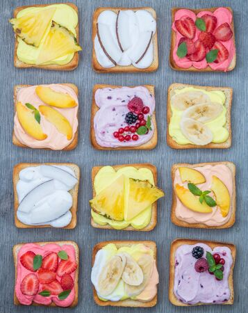 Assorted toasts with fruits and berries on wipped cream on a wood board on light background. Summer traditional homemade dessert