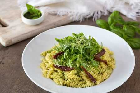 Colored pasta with rukola and basil on white plate with sauce