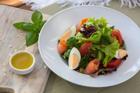 Vegetable salad with egg and salmon served with basil and topping sauce. 写真素材