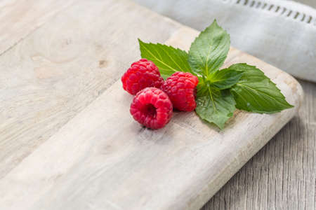 Fresh red raspberries on wooden background. Close up photo of the fresh berries. Harvest Concept.
