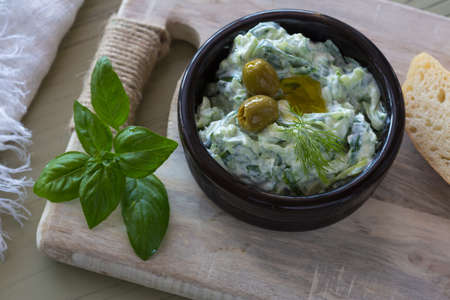 Greek dip sauce or dressing tzatziki and ingredients decorated with olive oil and basil on wooden table.