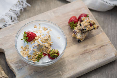 Bowl of fresh strawberries and yogurt. Photo of breakfast bowl with farm fresh strawberries and granola served on a wooden board 写真素材