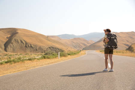 Hitchhiker traveler woman on the road in sunset. Girl traveler hiker on the road. Summer vacation. Freedom 写真素材