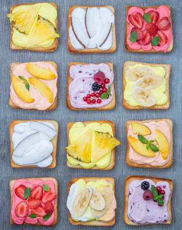 Assorted toasts with fruits and berries on wipped cream on a wood board on light background. Summer traditional homemade dessert Archivio Fotografico - 151310941