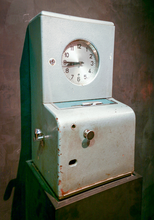 An old time clock for employees to keep track of their working hours photo