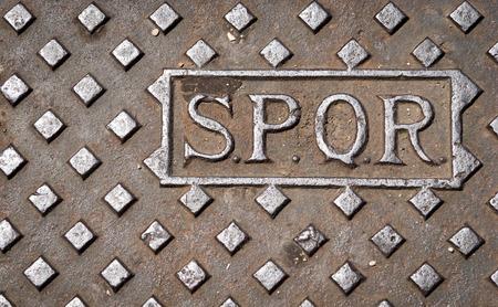 spqr: Una tapa de alcantarilla de drenaje en Roma, Italia, con las letras SPQR.