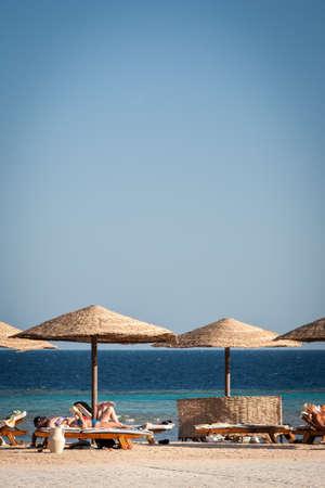 HURGHADA, EGYPT - NOVEMBER 21, 2006: Tourists lazing on sun loungers on the  coast of Red Sea near Hurghada, Egypt.