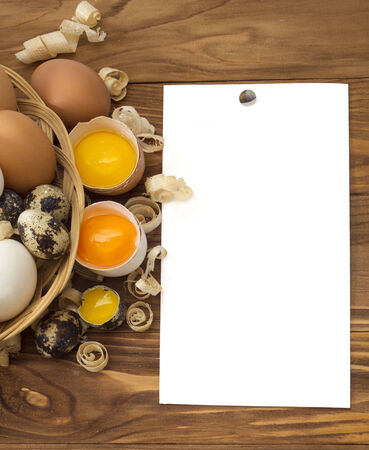 chicken and quail eggs on wooden background with paper for text photo