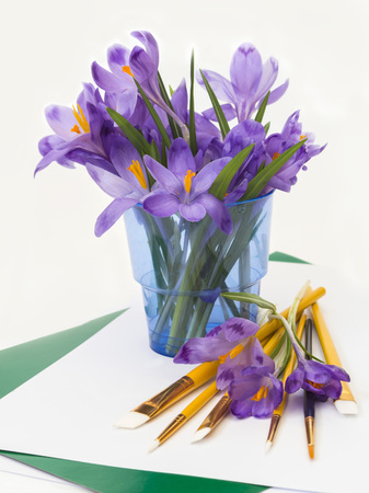 Postcard  purple spring crocus flowers in a glass with brushes for painting. photo