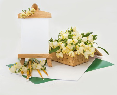 postcard white snowdrops basket and a small easel brushes for