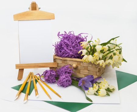 Postcard, white snowdrops basket and a small easel, brushes for painting. photo