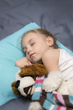 diseased: school age girl sleeps with his a favorite toy dog Stock Photo