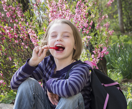 Happy little girl with lollipop outdoors in spring photo