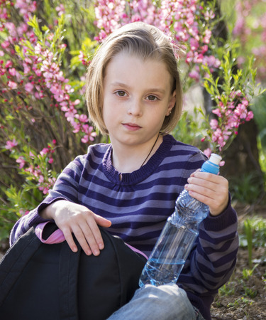 Little schoolgirl  drinks water from a plastic bottle outdoors in spring photo