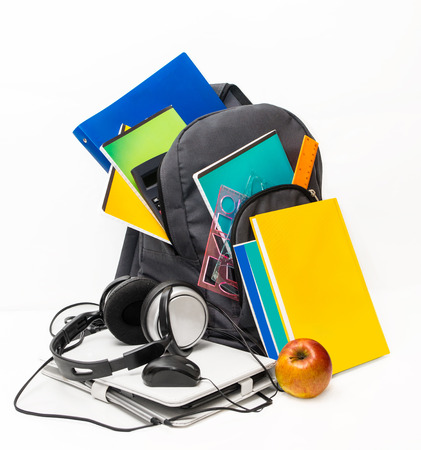 School backpack  with school supplies and a tablet with headphones. Notebooks, tablet, headphones, ruler, book, apple. photo