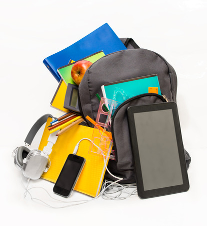 School backpack with school supplies and a tablet with headphones. School backpack , notebooks, tablet, headphones, ruler, book, apple. photo