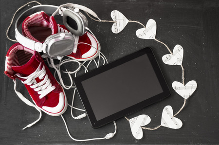 Love for music concept. Red sneakers, headphones, tablet and hearts with notes on the blackboard. photo
