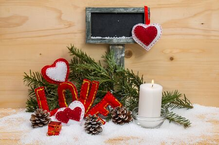 burning love: Hearts and the word love made of cloth with burning candle and a sign for text on wooden background. Symbol of love.