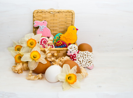 easter cookie: Easter cookie in a basket of flower Narcissus and chicken egg on wooden background Stock Photo