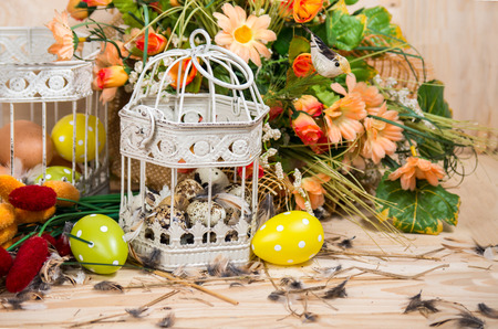 Easter still life. Bird cage with quail eggs and spring flowers on a wooden background photo