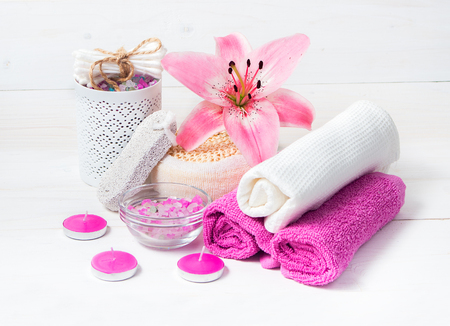 spa flower: Spa concept. Pink lily flower,sea salt, candles,towels  and objects for spa procedures on a white wooden background. Stock Photo