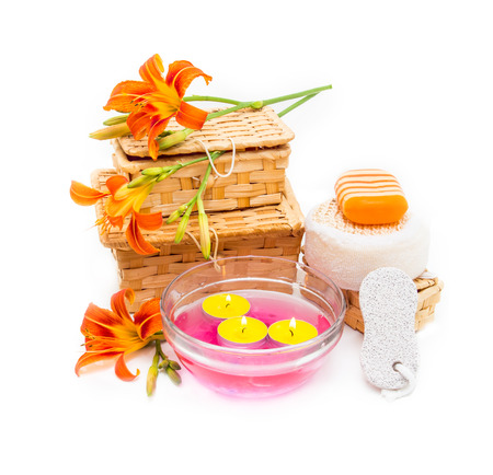 the candle: Spa concept. Orange lily flowers, boxes, sea salt, candles, soap  and objects for spa procedures on a white background