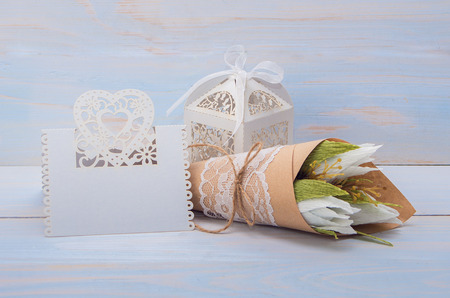 felicitation: decorative flowers and gift with a card for text on wooden background