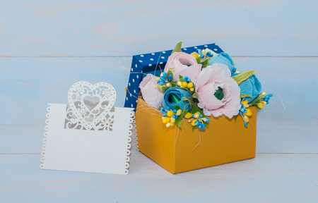 felicitation: decorative flowers in a gift box with a card for text on wooden background