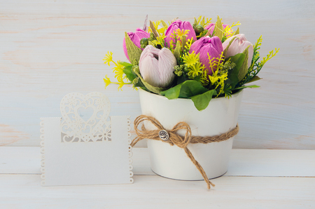 felicitation: Decorative flower in a pot and gift with a card for text on wooden background Stock Photo
