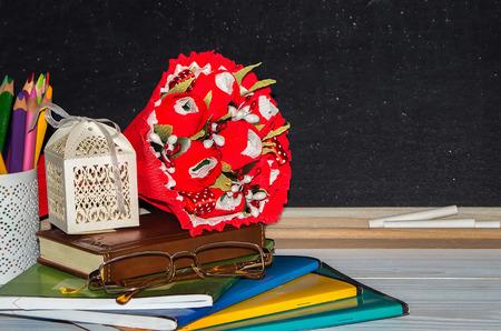 ramo de flores: D�a Maestro. Flores y regalos, cuadernos en la mesa del profesor. (flores, regalo, vasos, cuadernos, tablero, l�pices).