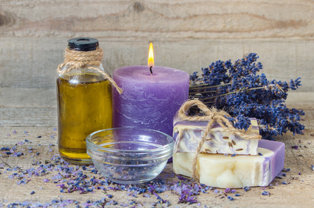 Spa lavender concept. Lavender oil, lavender flowers, handmade soap and  sea salt with burning aromatherapy candle.