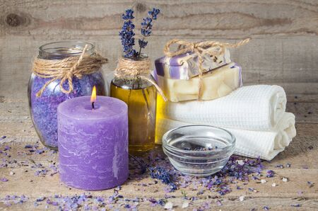 aromatherapy candle: Spa lavender concept. Lavender oil, lavender flowers, handmade soap  and bath towels, sea salt and a burning aromatherapy candle.