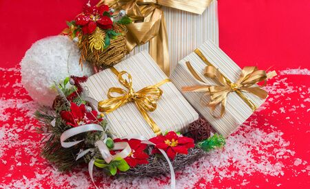 Christmas background with gifts .Boxes with ribbon and wreath with poinsettia flowers on a red background with snow. Stock Photo