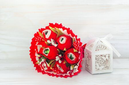felicitation: Decorative bouquet of flower red color and gift box on wooden background . Stock Photo
