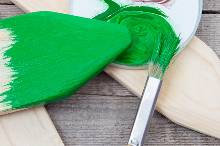 repaint: Paintbrush and green paint for painting wooden products Stock Photo