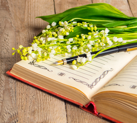 deliberate: Flowers lily of the valley on the book for records and a pen on a wooden background. Soft focus, deliberate slight blurring .