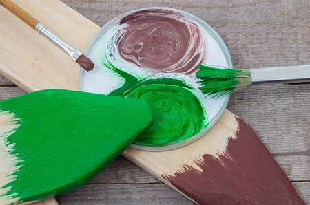 green brown: Paintbrush and green, brown paint for painting wooden products Stock Photo