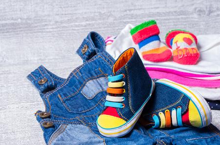 fondo para bebe: zapatos infantiles para bebés y un conjunto de ropa en el fondo