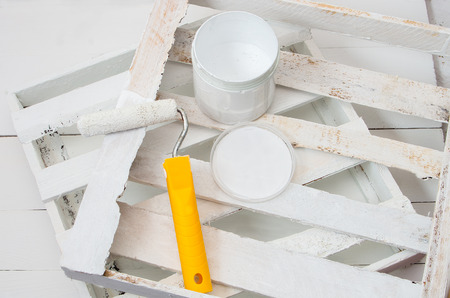 repaint: painting roller and white paint for painting wooden planks