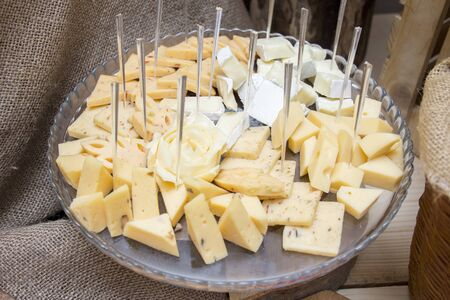 slicing cheese platter on a wooden plate