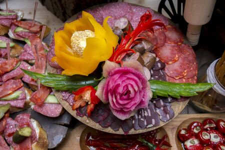 sliced assorted cured meat and sausages decorated with carved flowers of vegetables on a wooden plate