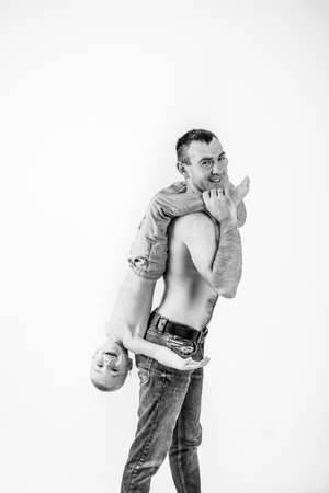 father playing with son. boy laughing happily riding on dad's back. black and white photo