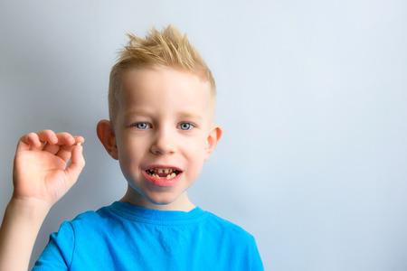 Baby met melk tand in handen Stockfoto